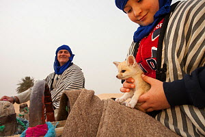 Young boy holding Fennec fox (Vulpes zerda) pup aged few weeks, caught in the wild and shown at a famous camel trekking site for tourists in the hope of either selling it or being paid for photos, Keb... - Bruno D'Amicis