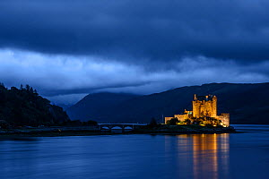 Eilean Donan Castle lit up at twilight with dark clouds. Scotland, UK, September 2013.  -  Sven  Zacek