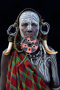 Portrait of woman from the Mursi tribe, traditionally decorated and painted, wearing a large clay lip plate, Omo Valley, Ethiopia, March 2015. - Eric Baccega