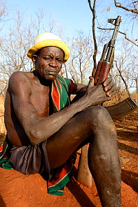 Older man from the Bodi tribe displaying elaborate skin scarifications, and holding Kalashnikov gun. The ones on his shoulder are for enemies he killed, the circles on the arm are for big game he hunt... - Eric Baccega