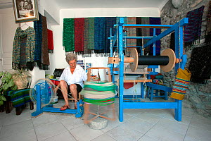 Lady spinning on manually operated wheel, inside her shop, with scarves she made, Mykonos Town, Cyclades, Aegean Sea, Mediterranean, Greece, August 2007. - Constantinos Petrinos