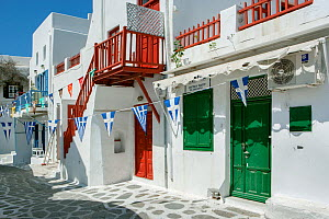 Picturesque alley in Mykonos Town with white houses, green doors and red balconies decorated with the Greek flag bunting, Mykonos Island, Cyclades, Aegean Sea, Mediterranean, Greece, August 2007. - Constantinos Petrinos
