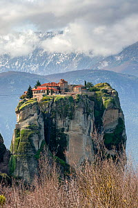 Holy Trinity Monastery,  Greek Orthodox rock monastery in Meteora. In the background the Pindus Mountain Range with snow on its slopes. Meteora, Kalambaka, Thessaly Region, Greece, Mediterranean, Febr...  -  Constantinos Petrinos
