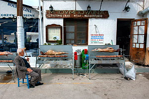 Man sitting outside a taverna, watching  whole lamb and Kokoretsi (offal sausage) cooking on a spit, in preparation for Easter Sunday meal. Spetses Island, Aegean Sea, Greece, Mediterranean, April 200...  -  Constantinos Petrinos