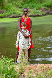 Young boy dressed in safari clothes with Samburu warrior dressed in the traditional red clothes,  Masai Mara National Reserve, Kenya, Africa, August 2012.  -  Constantinos Petrinos