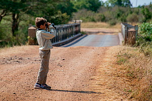Young boy dressed in safari clothes using a pair of binoculars,  Masai Mara National Reserve, Kenya, Africa, August 2012. Model released  -  Constantinos Petrinos