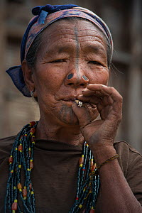 Apatani woman smoking with facial tattoos and traditional nose plugs / Yapin Hulo.These plugs are made of a cane slice. This practice was to make them look unattractive to males from other tribes. The... - Pete Oxford