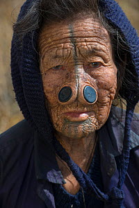 Apatani woman with facial tattoos and traditional cane nose plugs / Yapin Hulo made to make them look unattractive to males from other tribes. These facial modifications are  now  outlawed. Apatani Tr... - Pete Oxford
