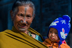 Apatani woman with facial tattoos and traditional nose plugs / Yapin Hulo holding baby. These plugs are made of a cane slice. This practice was to make them look unattractive to males from other tribe...  -  Pete Oxford