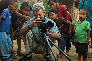 Photographer Pete Oxford with Naga head hunters children watching him take photos. Nagaland,  North East India, October 2014. - Pete Oxford