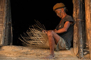 Konyak Naga tattooed head hunter making a basket. Only someone who has killed and taken a human head can be tattooed in this manner. Mon district. Nagaland,  North East India, October 2014.  -  Pete Oxford