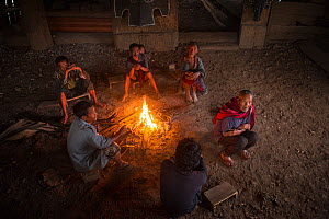 Men sitting around fire in Konyak Naga Morong or communal house. Mon district, Nagaland, North East India, October 2014.  -  Pete Oxford