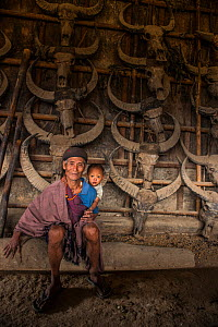 Konyak Naga man with grandson, in house decorated with buffalo skulls, Mon district, Nagaland, North East India, October 2014.  -  Pete Oxford