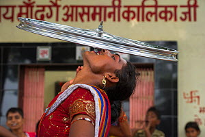 Hijra performer, balancing bicycle wheel on teeth. Hijra are transgender people, legally recognized as a third gender in India.  Uttar Pradesh, India, October 2014.  -  Pete Oxford