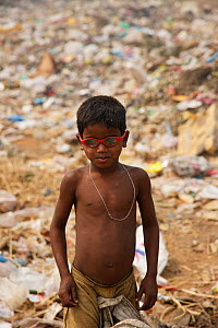 Young rag-picker boy with sunglasses at landfill site,  Guwahti, Assam, India, March.  -  Tony Heald