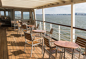 Empty chairs and tables on upper deck of Mersey Ferry, Liverpool, Merseyside, England, UK. June 2014. All non-editorial uses must be cleared individually. - Norma  Brazendale