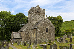 St. Cadoc's Church, with lichen covered headstones in graveyard, Cheriton, Gower, South Wales, UK, June 2015.  -  Chris  Mattison