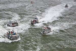 Large number of fishing boats fishing for Sockeye salmon (Oncorhynchus nerka) using drift gill nets, and trying to out  manoeuvre other boats.  Naknek River, Bristol Bay, Alaska, USA, July. - Jeff Rotman