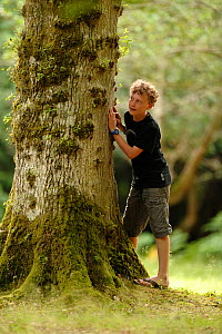 Boy standing next to Oak tree (Quercus) Bolderwood Arboretum Ornamental Drive in Lyndhurst, Hampshire, UK, July. Model released. - Solvin Zankl