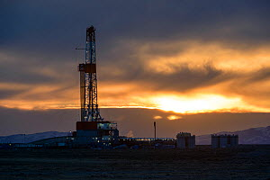 Natural gas drilling rigs on Pinedale Mesa at sunset, Sublette County, Wyoming, USA. May. - Gerrit  Vyn