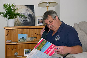 British Divers Marine Life Rescue regional co-ordinator Dave Jarvis reading report of an injured grey seal pup (Halichoerus grypus) on a Cornish beach from his home, Cornwall, UK, October.  Model rele...  -  Nick Upton