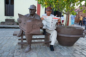 Cuban man reading a newspaper, sitting with statue of himself in the same pose. The government of Camaguey commissioned sculptures of normal citizens around the town.  Plaza del Carmen, Camaguey, Cuba...  -  Franco  Banfi