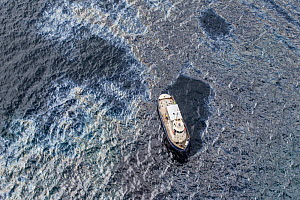 Oil slick and sheen on the sea surface around a service vessel, two days after the container ship MV Rena became grounded on Astrolabe Reef, off of the Port of Tauranga, Bay of Plenty, New Zealand, Oc...  -  Brent  Stephenson