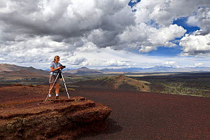 Vicky Spring taking photographs of the wilderness trail on Inferno Cone, in Craters Of The Moon National Monument, Idaho, USA 2015. July. Model released. - Kirkendall-Spring