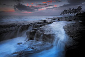 Long exposure of tidal water flowing off rocks, with the Okshornan Mountains in the background, Isle of Senja, Troms, Norway, February 2015. - Benjamin  Barthelemy