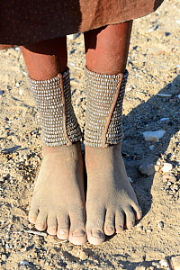 Close-up of traditional Himba woman foot ornaments - 'Omohanga', a 21 strand layered anklet made with metal beads, indicating if she is married and has children, Marienfluss Valley. Kaokoland, Namibia...  -  Eric Baccega