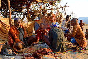 Elderly himba men and woman gathering in the morning in the village chief's hut, Marienfluss Valley, Kaokoland Desert, Namibia. October 2015 - Eric Baccega