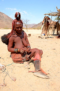Himba woman adjusting her traditional 'Omohanga' foot ornament, a 21 strand layered anklet, indicating if she is married and has children, Marienfluss Valley. Kaokoland, Namibia October 2015 - Eric Baccega