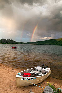 Doug Anderson fishing on Stanley Lake during rain shower, with rainbow, Stanley Lake National Recreation Area, Idaho, USA. July 2015. Model released.  -  Kirkendall-Spring