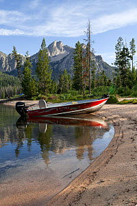 Boat beached on shore of Stanley Lake with McGowin Pear in distance, Sawtooth National Recreation Area, Idaho, USA. July 2015.  -  Kirkendall-Spring