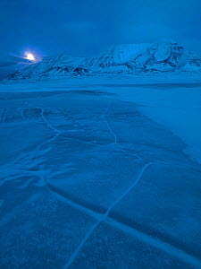 First light in Svalbard with moon low against mountains, near Longyearbyen, Norway, February. - Pal Hermansen