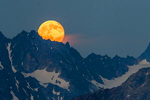 Full moon rising over the Verpeilspitze (3430m). This peak is part of the Glockturmkamm, the westernmost ridge of the Otztal Alps. Nordtirol, Austrian Alps. July. Digitally stitched panorama.  -  Alex  Hyde