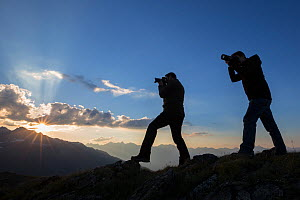 Photographers at sunset recording the mountain landscape of the Samnaungruppe, a subgroup of the Central Alps, Nordtirol, Austrian Alps. July. - Alex  Hyde