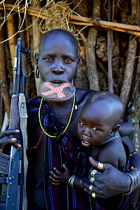 Mursi woman with clay lip plate, holding rifle and son. Mago National Park. Omo Valley, Ethiopia.  -  Enrique Lopez-Tapia