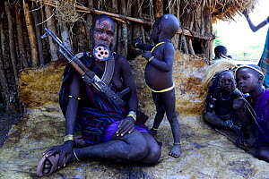 Mursi woman with clay lip plate  and children, armed with rifle. Mago National Park. Omo Valley, Ethiopia.  -  Enrique Lopez-Tapia