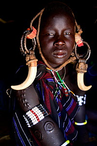 Young girl with scarification wearing traditional clothing. Mursi tribe, Mago National Park. Omo Valley, Ethiopia.  -  Enrique Lopez-Tapia