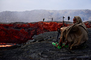 An armed soldier watching the activity of Erta Ale volcano crater at dawn. Afar Region, Ethiopia, Africa. November 2014.  -  Enrique Lopez-Tapia