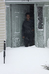 Woman looking out att Winter storm Jonas, Washington DC area, January 2016. This storm had winds up to 75 mph, over 30 people killed, up to 42 inches of snow - John Cancalosi