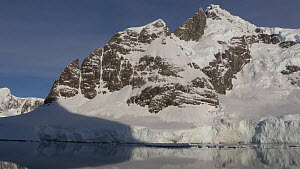 Tilt shot of a mountain and its reflection, seen from a boat passing through Lemaire Channel, Antarctic Peninsula.  -  Fred  Olivier