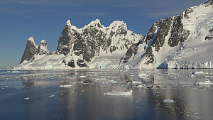 Panning shot of mountains and floating ice seen from a boat in Lemaire Channel, Antarctic Peninsula.  -  Fred  Olivier