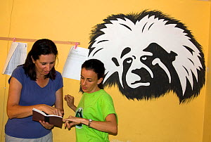 Anne Savage and Rosamira Guillen discussing business at the Project / Proyecto Titi office, with painting of a Cotton top tamarin (Saguinus oedipus)  Luruaco, Colombia. July 2008. Critically endangere...  -  Lisa  Hoffner