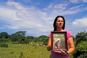 Anne Savage, director of Project / Proyecto Titi holding up picture of  Cotton top tamarin (Saguinus oedipus) in pasture which was once prime tropical dry forest habitat for the monkeys, Colombia. Jul...  -  Lisa  Hoffner