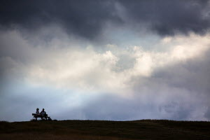 Man and woman talking on a bench with cloudy sky behind, Parliament Hill, Hampstead Heath, London, England, UK, July. - Matthew Maran