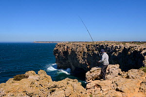Fisherman angling in the Atlantic sea from high cliffs at Ponta de Sagres, Algarve, Portugal, July 2013.  -  Nick Upton
