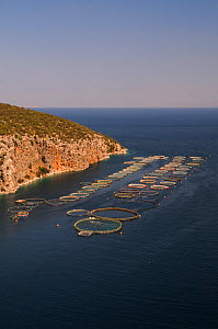 Landscape of fish farm with floating pens for Sea bass and Sea bream, Selonda Bay, Argolis, Peloponnese, Greece, August 2013. - Nick Upton