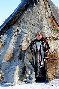 Carolina Serotetto, Nenet teenager at entrance of reindeer fur covered tent, warmly dressed in traditional coat. Yar-Sale district. Yamal, Northwest Siberia, Russia. April 2016.  -  Eric Baccega